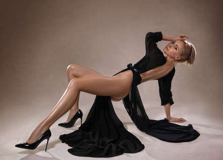 Foto de Beautiful blonde nude woman with perfect legs in black dress and high heels - fashion style on the studio background. - Imagen libre de derechos