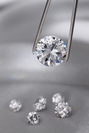 A round brilliant cut diamond held in tweezers