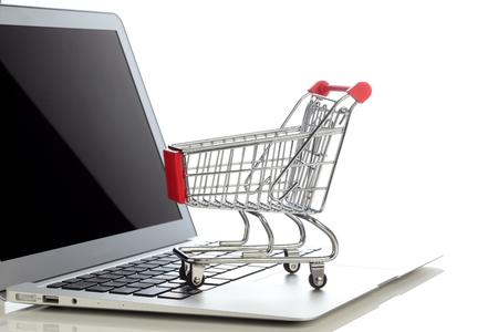 Photo pour E-commerce. Shopping cart on laptop. Conceptual image. - image libre de droit