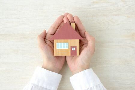 Photo pour A house model wrapped in a hand - image libre de droit