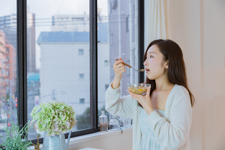 Lady in nightwear eating cereals