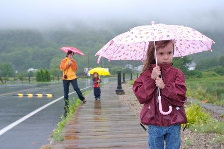 Family  mother, daughter and son  walking and playing under the rain with colorful umbrellasの写真素材