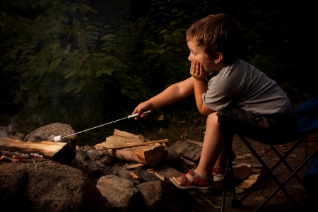 Little boy cooking a marshmallow over a campfire at night