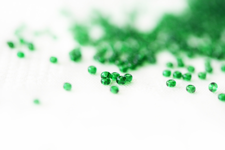 Green color seed beads scattered on textile background close up