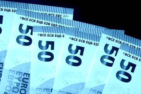 Photo for Fifty euro notes on a dark background close up. Blue color toned - Royalty Free Image