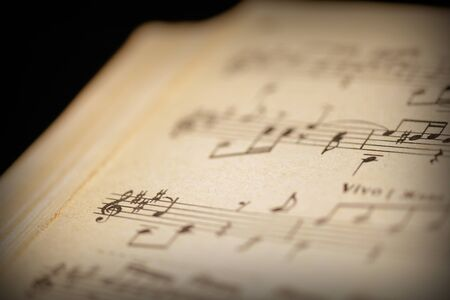 Photo pour Fragment of a page from an old musical notebook on a dark surface close-up. Music background retro style toned - image libre de droit