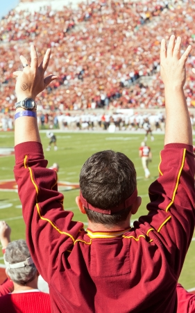 Tallahassee, Florida, USA - October 22, 2011:  Florida State football fan stands up and cheers at a home game as the FSU Seminoles play the Maryland Terps at Doak Campbell Stadium.