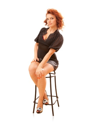 pin-up - attracive young slim red-head woman on a bar stool