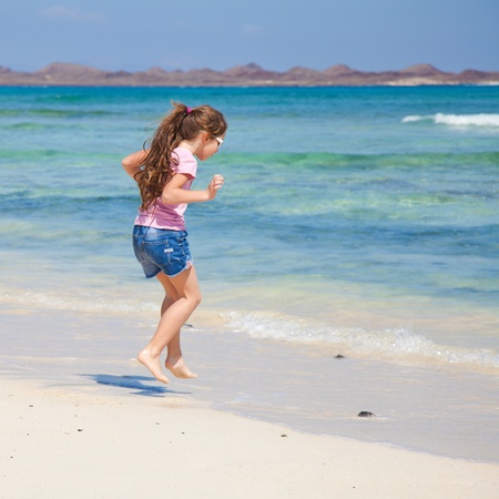 little girl with long brown hair in ponytail in pink t-shirt and denim shorts by the oceanの写真素材