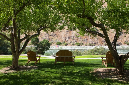 Three wooden pieces of outdoor furniture are placed in the shade of fruit trees on the grassy bank of a hill looking down on the swift rapids of the Snake River in Idaho.