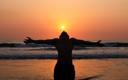 A young man stands as a living shadow  in front of the ocean with his arms outstreatched to the orange sky and his head tilted back to absorb the setting sun