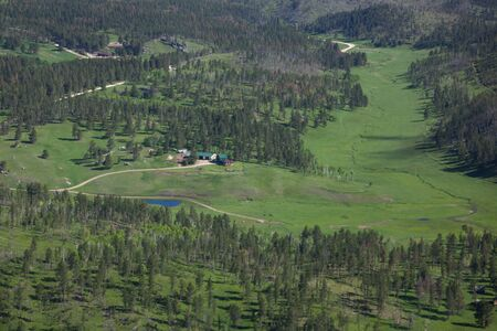 BLACK HILLS, SOUTH DAKOTA - June12, 2014:   An aerial view of a secluded ranch house in a green meadow with a winding creek and pine trees in the Black Hills, SD on June 12, 2014.