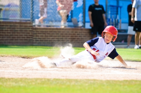 Youth baseball player sliding in at home