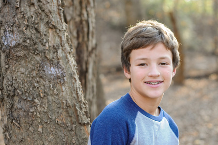Photo for Young handsome boy with braces, smiling next to tree - Royalty Free Image
