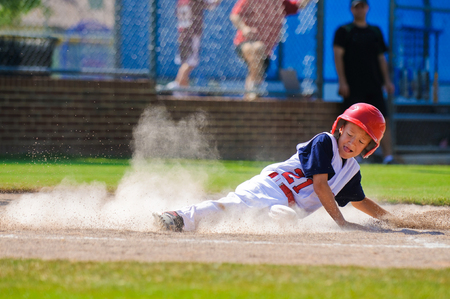 Photo pour Youth baseball player sliding in at home. - image libre de droit