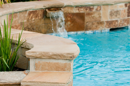Photo pour Beautiful swimming pool with flagstone wall that has waterfall pouring out of it. - image libre de droit