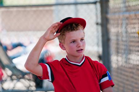 Teenage baseball boy in dugout reaching for ball cap.