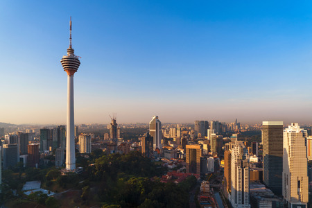 Foto de Menara Kuala Lumpur Tower with sunset sky. Aerial view of Kuala Lumpur Downtown, Malaysia. Financial district and business centers in urban city in Asia. Skyscraper and high-rise buildings at noon. - Imagen libre de derechos