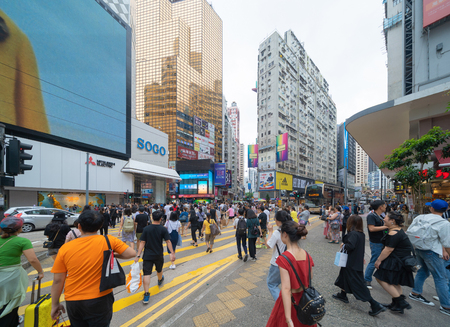 Foto de Crowd of people walking on street over zebra crossing or pedestrian crossing at shopping area with mall and department stores on street in Causeway Bay District, urban city of Hong Kong Downtown. - Imagen libre de derechos