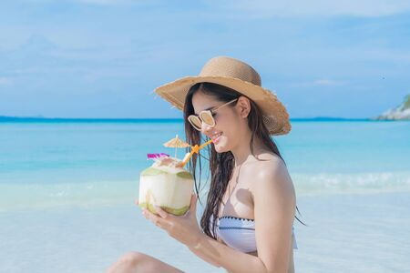 Photo pour Happy Asian woman, a sexy Thai lady, drinking coconut water at turquoise sea near Phuket beach during travel holidays vacation trip outdoors at natural ocean or island at noon, Thailand. - image libre de droit