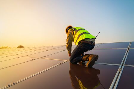 Photo for Portrait of engineer man or worker, people, with solar panels or solar cells on the roof in farm. Power plant with green field, renewable energy source in Thailand. Eco technology for electric power. - Royalty Free Image