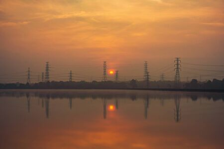 Photo pour High voltage metal post in the industrial estate with the sun and reflection at sunset. Electricity tower. Factory industry in energy or environment concept. Lampang City, Thailand. - image libre de droit