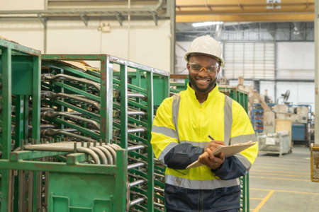 Photo for Portrait of Black African American man, an engineer or worker, with safety outfit checking quality control of product, car seat manufacturing factory industry plant in warehouse store. People. - Royalty Free Image