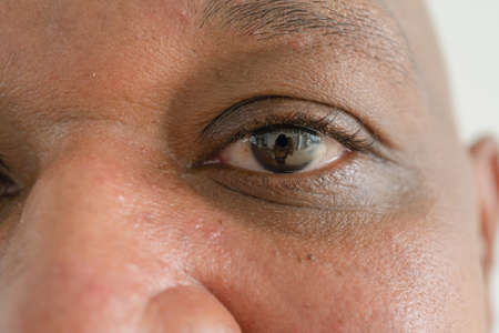 Photo pour Close up of Black African American elderly black man eyes. Texture of the black eye is visible. Macro detail of iris. - image libre de droit