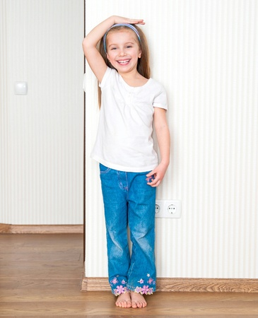 little girl measures the growth near the wall