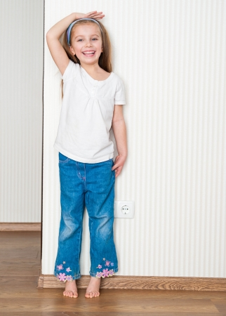 little girl measures the growth near the wall at home