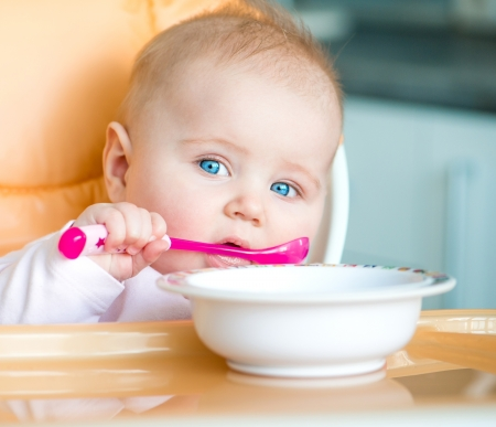 smiley baby girl is holding a spoon in her mouth and going to eat