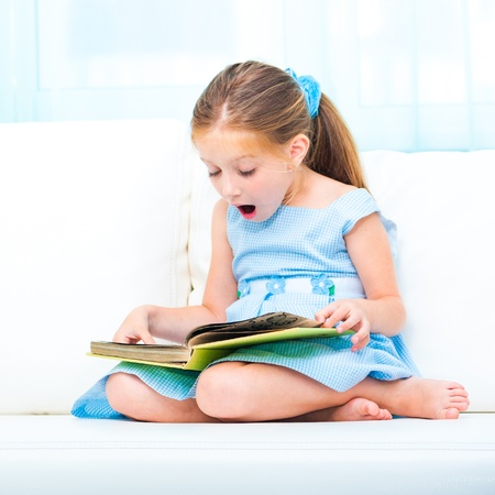 little cute girl reading a book and siting on the sofa