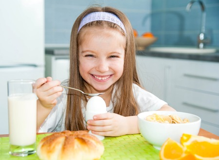 pretty little girl eating egg in the kitchen