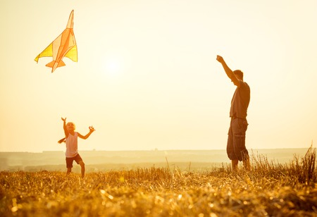 Dad with his little daughter let a kite in a field