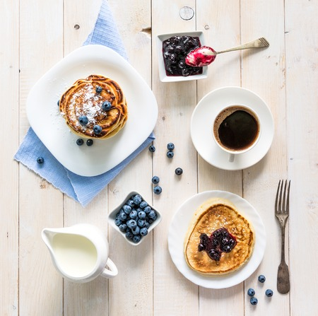 pancakes with blueberry and coffee on wooden background. top view
