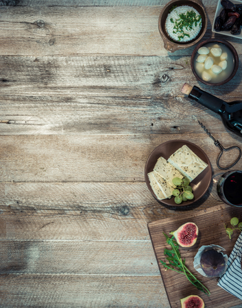 cheeses and brown bread on wooden table with text space