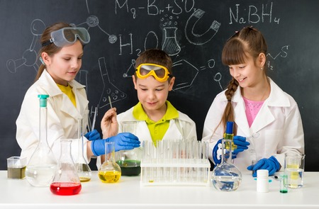 three little students on chemistry lesson in lab doing an experiment