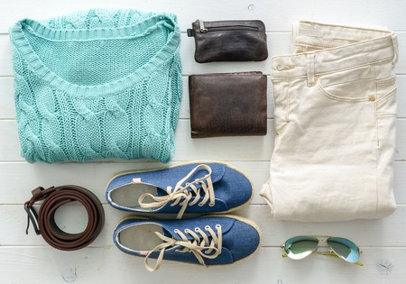 Foto de carefully folded woman casual closes and accessories on wooden table top view - Imagen libre de derechos