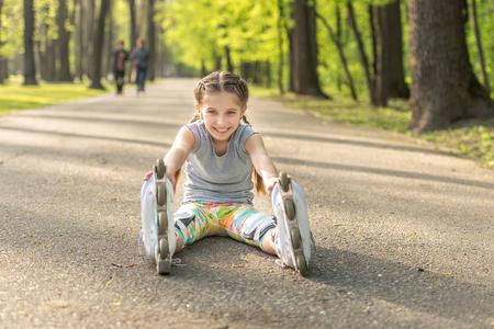 girl rollerblading sitting on asphalt, stretching