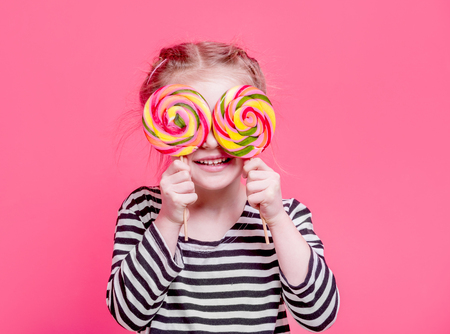Kid girl with lollypops in front her eyesの写真素材
