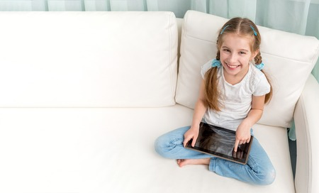 Photo pour cheerful little girl with tablet on her legs looking at camera - image libre de droit