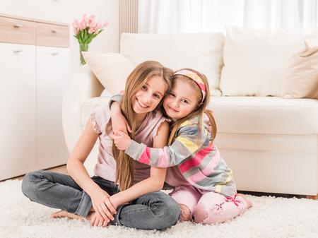 Photo pour Two sisters sitting in embrace - image libre de droit
