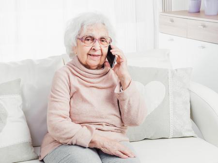 Photo pour Great-grandmother talking by smartphone - image libre de droit
