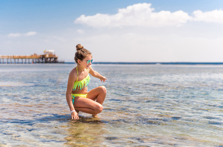 Photo pour Funny girl playing with water at beach - image libre de droit