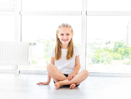 Foto de Female kid smiling, sitting on the floor - Imagen libre de derechos