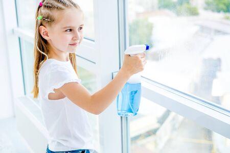 Photo pour Little girl cleaning the window - image libre de droit
