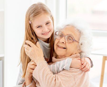 Photo pour Little girl embracing grandmother - image libre de droit