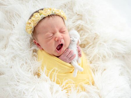 Photo pour Yawning newborn holding toy - image libre de droit