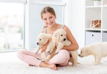 Foto de Girl hugging group of retriever puppies - Imagen libre de derechos