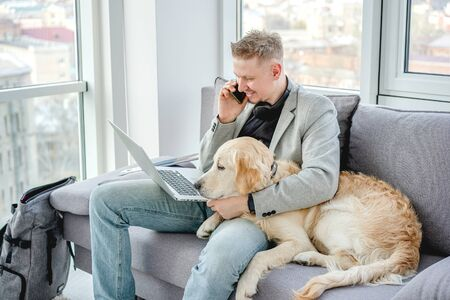 Photo for Handsome man cuddling dog while working - Royalty Free Image
